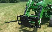Model WOFLSO-907 tractor loader mounted round bale unroller.